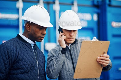 Engineers tracking inventory together in a commercial freight shipyard