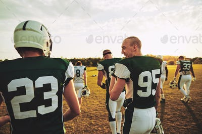 American football teammates walking off a laying field after practice