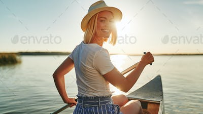 Smiling woman paddling her canoe on a lake in summer
