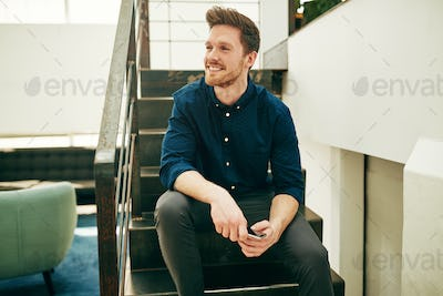 Smiling young businessman sitting with his cellphone on office stairs