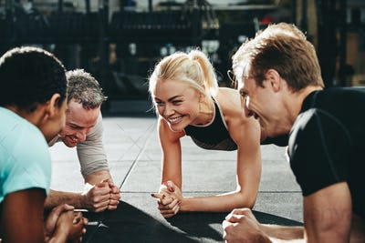 Diverse friends smiling while planking together on a gym floor