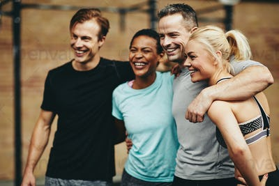 Laughing group of diverse friends standing together in a gym