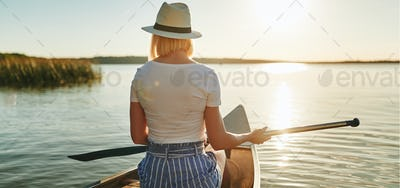 Young woman enjoying the view while canoeing on a lake