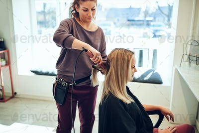 Hairstylist straightening a young woman's hair in her salon