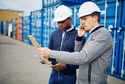 Two engineers tracking containers in a freight shipping yard