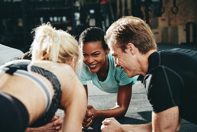 Diverse friends smiling while planking together during a gym workout