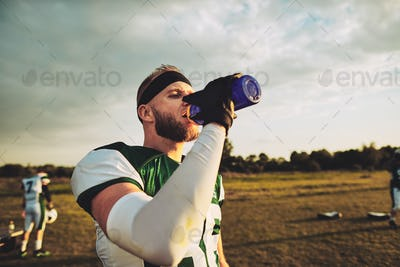 American football player drinking water during a team practice