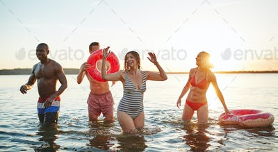 Diverse young friends wearing swimsuits having fun in a lake