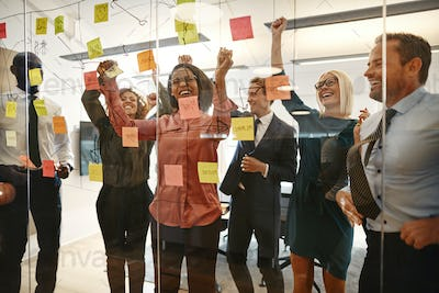 Cheering businesspeople celebrating together after an office brainstorming session