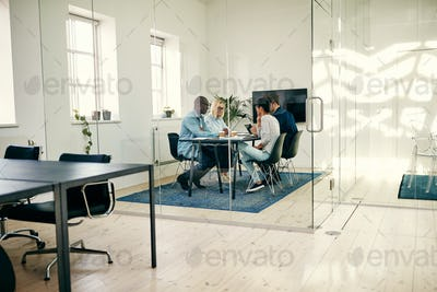 Diverse group of businesspeople sitting in a boardroom discussing work