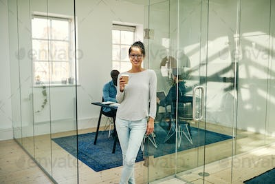 Smiling Asian businesswoman standing in an office enjoying a coffee