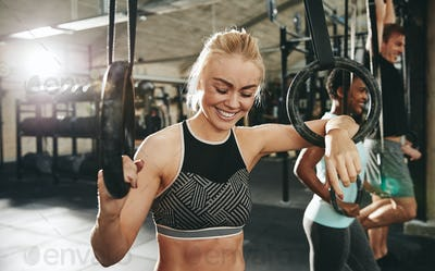 Laughing young woman working out with rings at the gym