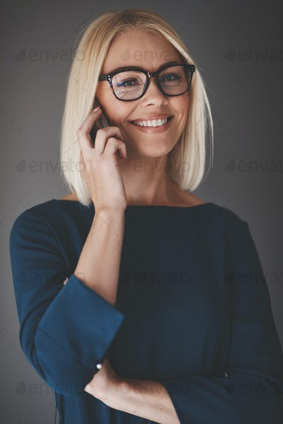 Smiling businesswoman talking on her cellphone against a gray background