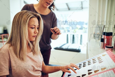 Young woman choosing a new hair color with her hairdresser