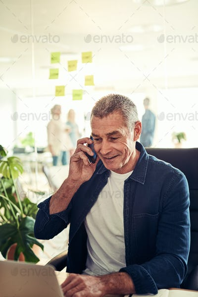 Smiling businessman sitting in his office talking on a cellphone