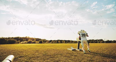 Lone football player doing tackling drills on a sports field