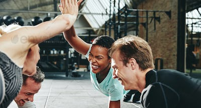 Laughing women planking and high fiving together while working out
