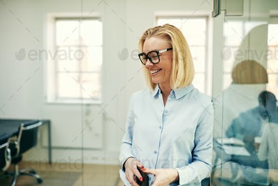 Laughing businesswoman holding a cellphone in a modern office