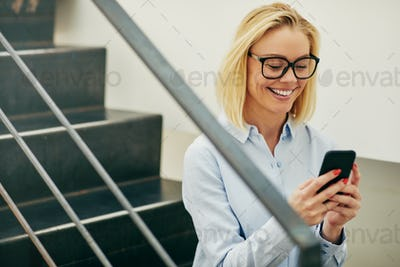 Smiling young businesswoman sitting on office stairs reading text messages