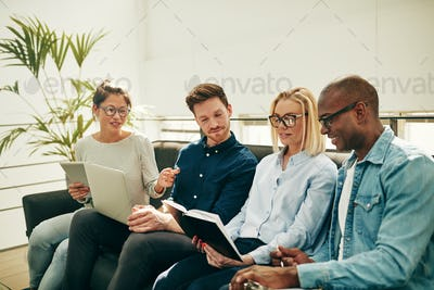 Diverse businesspeople talking together on a sofa in an office
