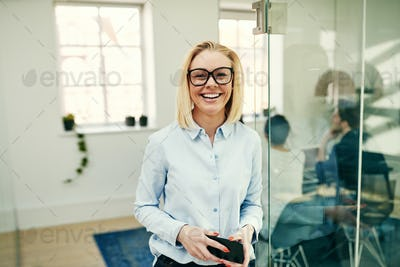 Young businesswoman laughing while standing in a bright modern office