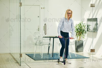 Laughing young businesswoman pushing a scooter around an office