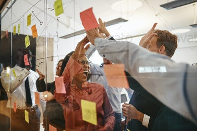 Cheering businesspeople high fiving together during a brainstorming session