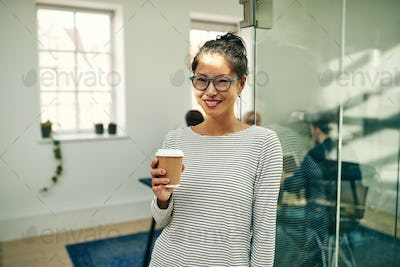 Smiling young Asian businesswoman drinking coffee during her office break