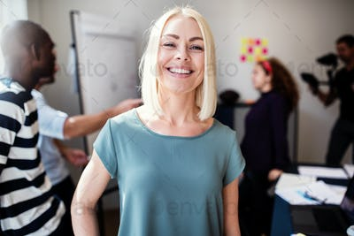 Smiling designer standing in an office with coworkers behind her