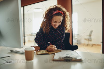 Laughing businesswoman writing down notes while working at her desk