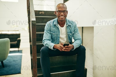 Smiling African businessman sitting on office stairs using a cellphone