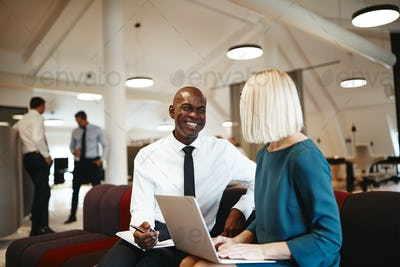 Diverse businesspeople smiling while working together in a modern office