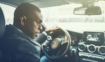 Young African businessman driving through city traffic
