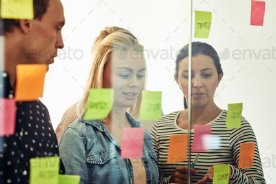 Group of smiling office colleagues brainstorming with sticky notes