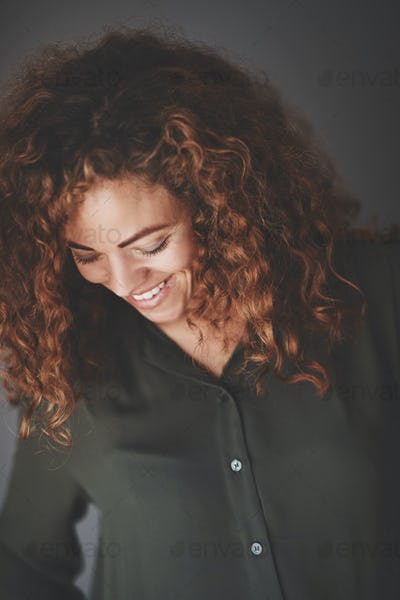 Young businesswoman laughing while standing against a gray background