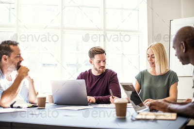 Group of designers discussing work around an office table