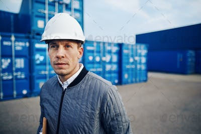 Port manager standing by freight containers on a commercial dock