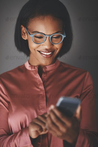 Smiling African businesswoman using her cellphone against a gray background