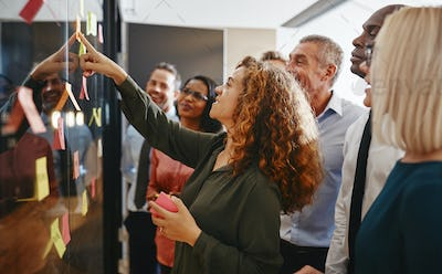 Diverse businesspeople brainstorming with sticky notes in an office