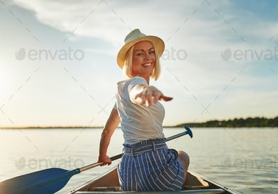 Smiling young woman enjoying a sunny day canoeing in summer