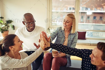Diverse group of coworkers high fiving together in an office