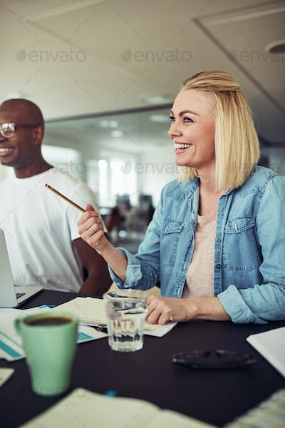 Young businesswoman laughing during a meeting in an office