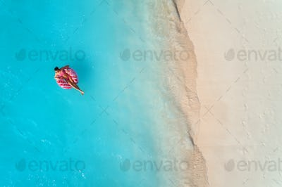 Aerial view of a swimming woman in the sea at sunset