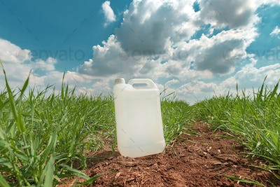 Blank pesticide jug container mock up in wheatgrass field