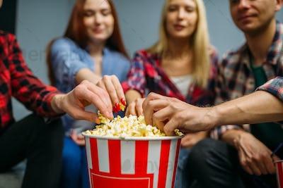 Group of people eating popcorn in cinema