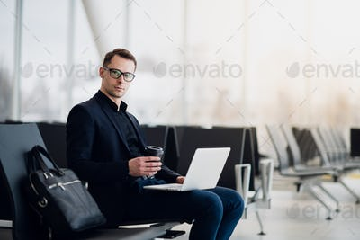 A business man sitting at the airport park working with his laptop and drinking takeaway coffee