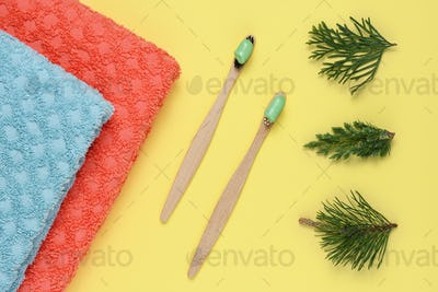 Bamboo toothbrushes with natural toothpaste on yellow background top view
