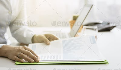 Businesswoman checking financial reports and statements