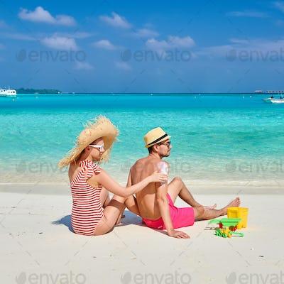 Woman applying sun screen lotion on man's back
