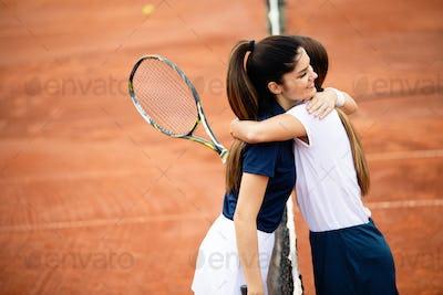 Women tennis player handshaking after playing a tennis match. Fairplay, sport concept